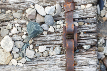metal bracket with a buckle on the old railway sleepers. different textures close