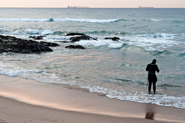 Man wearing wet-suit standing in the surf close to rocks, with ships on the horizon.
