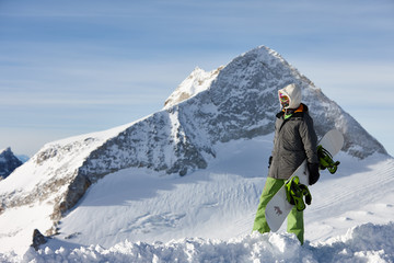Young snowboarder watching snowy mountain peaks landscape