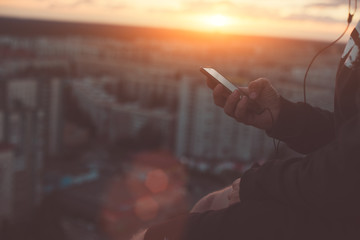 Man with smartphone in hands listening music on the roof at sunset, lens flares