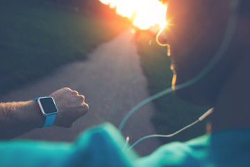 Athlete in the park looking at smart watch before running