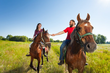 Happy young couple riding bay horses holding hands