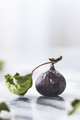 Fig with a leaf, on a marble background.