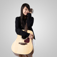 Teenage asain girl hugging her acoustic guitar, Isolated on grey background