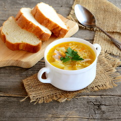 Chicken soup with noodles, potatoes, onions and carrots. Chicken soup in a bowl, sliced bread, spoon on old wooden table. Rustic style. Closeup