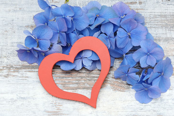 blue flower and red heart lying on wood