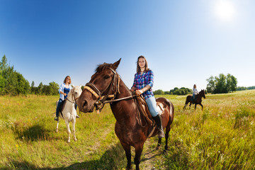 Three female equestrians riding horses in field