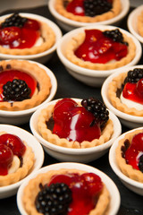 mini cherry pies/tarts on  plates garnished with blackberry