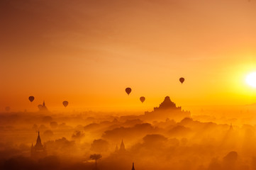 Amazing misty sunrise colors and balloons silhouettes over ancient Dhammayan Gyi Pagoda. Architecture of old Buddhist Temples at Bagan Kingdom. Myanmar (Burma). Travel landscapes and destinations