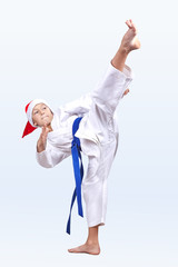 High blow leg karateka is beating in a cap of Santa Claus