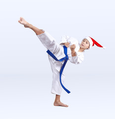 Roundhouse kick karate boy beats in a cap of Santa Claus