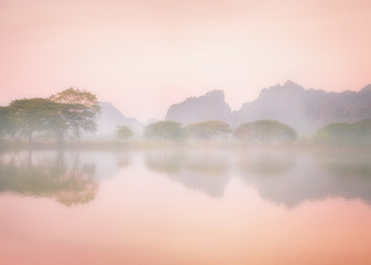 Amazing watercolor view of foggy morning landscape with trees reflection in lake water. Hpa An,...