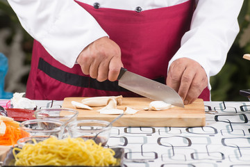 Chef slicing eringi for cooking