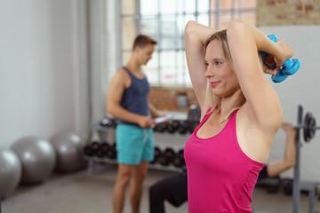 frau trainiert die armmuskulatur im fitnessstudio