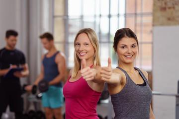 zwei frauen zeigen daumen hoch im fitness-club