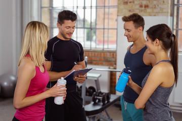 trainer berät sportler im fitnesstudio