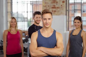 muskulöser mann im fitnessstudio mit team im hintergrund
