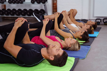 männer und frauen im fitness-kurs dehnen die beine