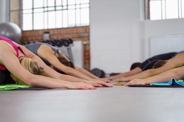 sportliche gruppe macht dehnübungen im fitness-studio