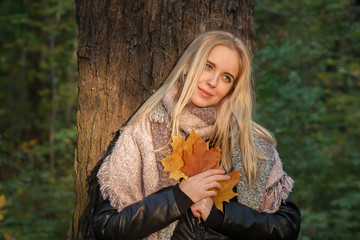 happy blond girl with maple leaves near tree, toned image