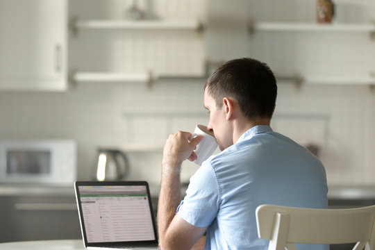 Portrait of a young man working at the desk with a laptop, looking at the screen, drinking from a mug. Education, business concept photo
