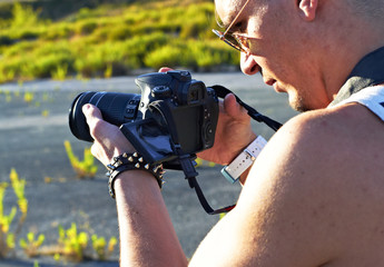 Young Man with reflex camera video recording