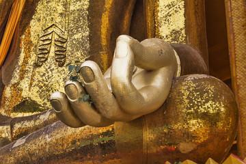 Golden Buddha hand on knee of statue closeup