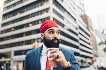 Businessman holding coffee cup in street, Manhattan, New York, USA
