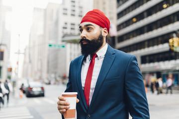 Businessman holding coffee in street, Manhattan, New York, USA