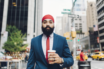 Indian businessman walking in Manhattan, drinking coffee