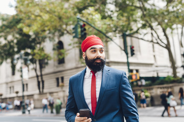 Indian businessman crossing street in Manhattan, holding smart phone