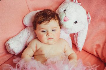 Little beautiful girl lying on the pink couch