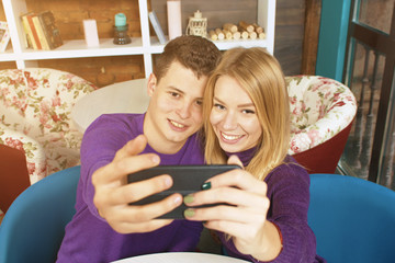 Young couple man and woman doing selfie. Home or a coffee shop