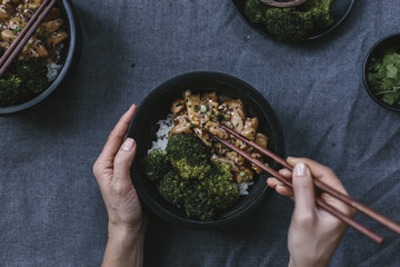 Chicken stir fry with roasted broccoli. Hands with chopsticks.