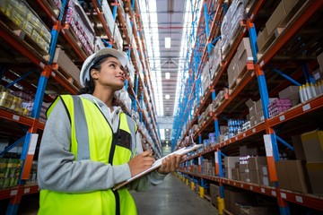 Female warehouse worker looking at packages