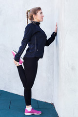Fitness woman doing  runner stretching standing against a wall