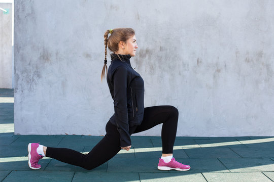 Fitness woman doing front  lunge, gray wall background