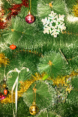 Christmas tree decorated with bright colorful toys, snowflakes. Under the tree are gifts of silver and gold gift bags and gift in a red-golden shiny packaging