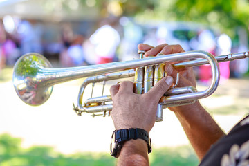 Hands of man playing the trumpet at outdoor