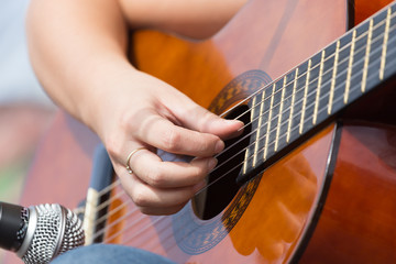 girl's hand playing guitar