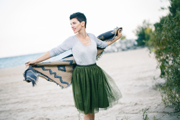 Portrait of beautiful smiling Caucasian brunette woman with short hair in green olive tutu tulle skirt, with large shawl scarf,  standing barefoot on beach looking away, freedom, happy lifestyle