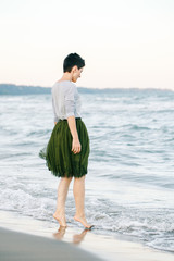 Portrait of beautiful Caucasian white brunette woman with short hair in grey shirt, green olive tutu tulle skirt, standing barefoot on beach in sea water, her back to camera, free happy lifestyle