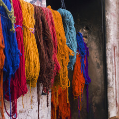 Bundles of various colours of yarn hanging against a wall