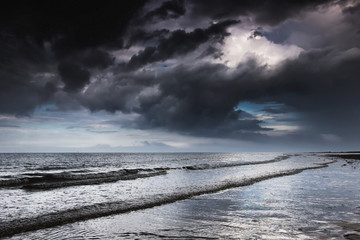 Dark storm clouds over the ocean with waves rolling into the shore;Druridge bay northumberland england