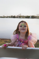 A young girl wearing a pink dress and accessories at the water's edge;Gold coast queensland australia