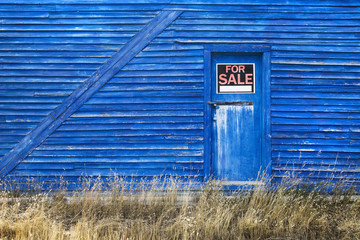 A blue barn with a for sale sign in the window of the door;Saskatchewan canada