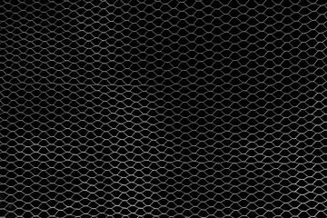 Silberner, filigraner Maschendraht vor einer schwarzen Wand