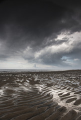 Rippled sand under a dark cloud at the water's edge;Northumberland england