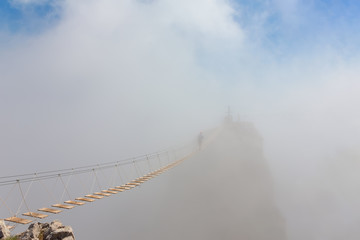 Man crossing the chasm on the hanging bridge in fog (focus on the middle of bridge)