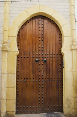 Wooden door decorated in rivets in an arch in the old medina;Casablanca morocco